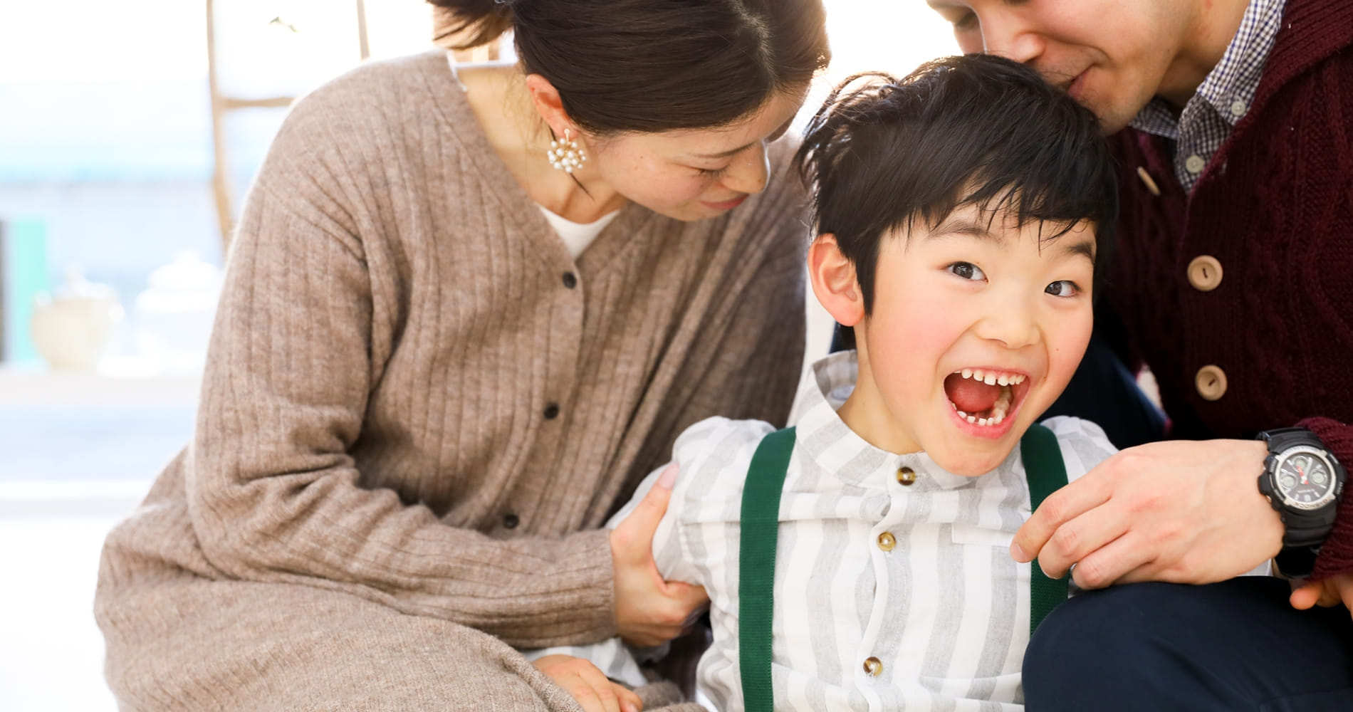 家族に抱えられている子どもの写真